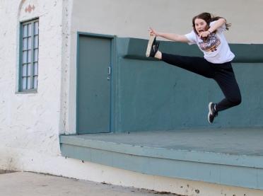Augustana freshman Maddy Deetz leaps off the stage at McKennan Park.