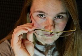 Lea gazes over her glasses.