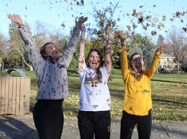 Linnea Ankeny, Maddy Deetz and Madison Hetland throw leaves in the air at McKennan Park.