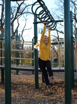 Madison Hetland moves through the monkey bars at McKennan Park.