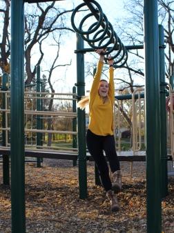 Madison Hetland moves through the monkey bars at McKennan Park.