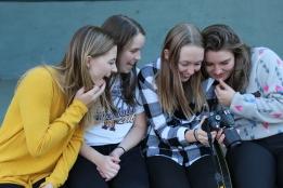 Augustana students Madison Hetland, Maddy Deetz, Keeley Meier and Linnea Ankeny check out a photo on Meier's camera.